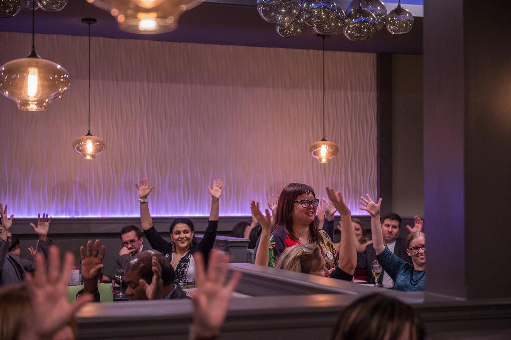 Participants waving hands at Cahoots Theatre SIGNature Gala